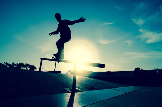Skateboarder silhouette on a grind