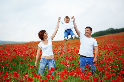 Happy young family baby resting in beautieful field of poppies