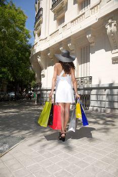 shopping woman back walking on sidewalk