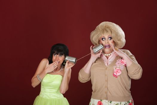 Retro-styled woman talks to drag queen on tin can phone