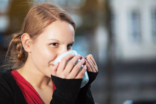 Pretty young woman drinking hot drink from a ceramic cup outdoors