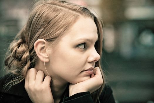 Profile of a pensive young blond woman, desaturated, film grain