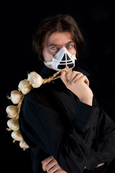Humorous shot of vampire in respirator holding garlic