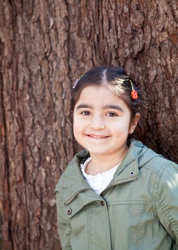 Portrait of a smiling happy little girl in front of a tree with bark texture in the background