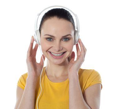 Pretty young female enjoying music, smiling at camera