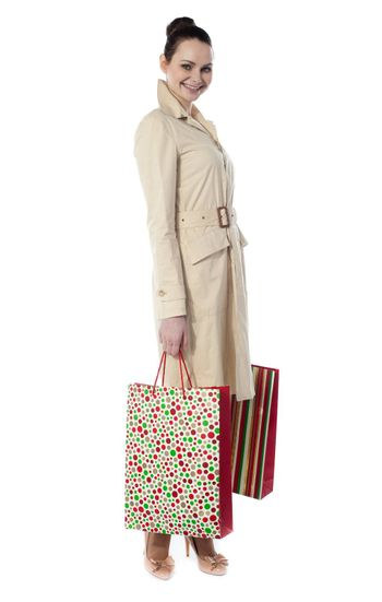 Beautiful happy shopping woman holding shopping bags isolated on white