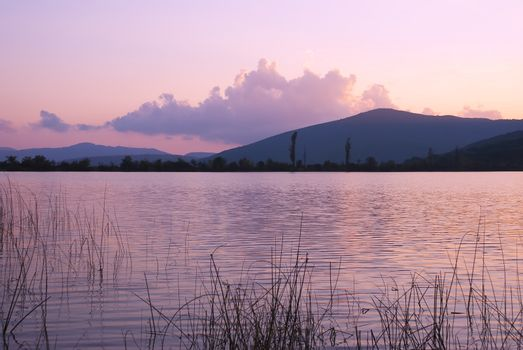 A calm evening landscape with lake and mountains
