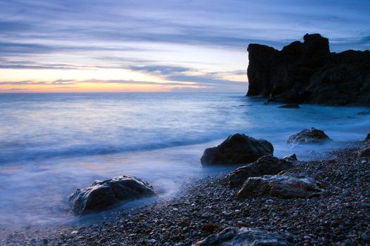 Beautiful rocky sea beach at the sunset