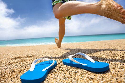 man running on the beach and slipper