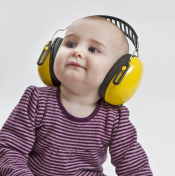 baby with yellow ear protection in loud environment. neutral grey background