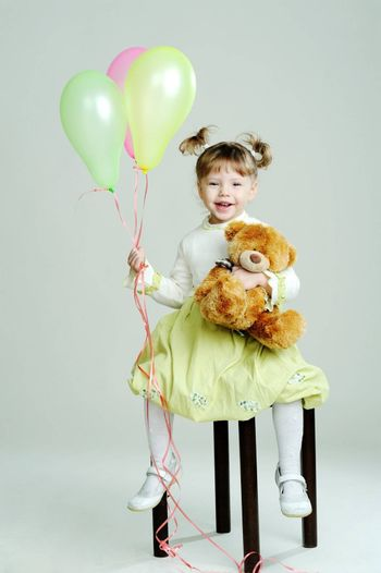 A portrait of a little girl with teddy-bear and balloons