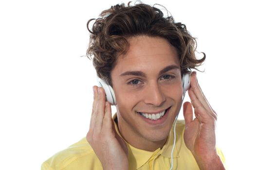 Casual young man listening music with headphones, isolated on white background