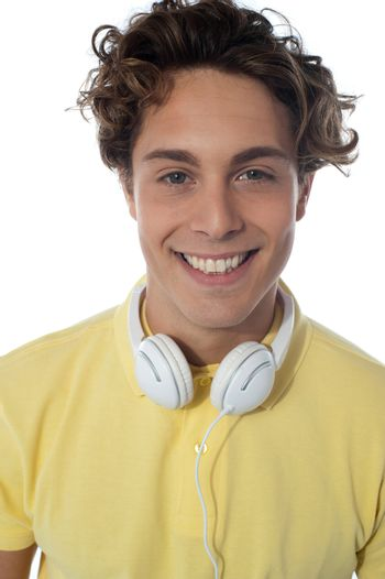 Guy with headsets around his neck smiling at you