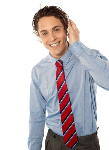 Relaxed young smiling male listening to music isolated on white