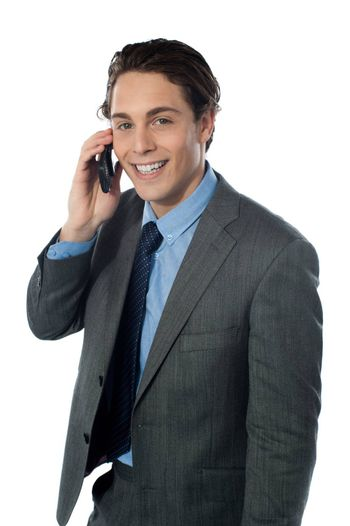 Portrait of a smiling businessman using a cellphone looking at you