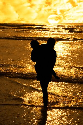 two girls in silhouette against a golden sunset one holding up the over with affection