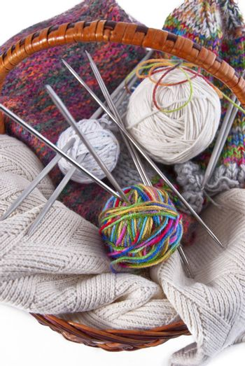 Balls of wool and knitting needles in basket on a white