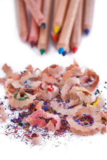 Multi-coloured pencil with crayon shavings, on white background