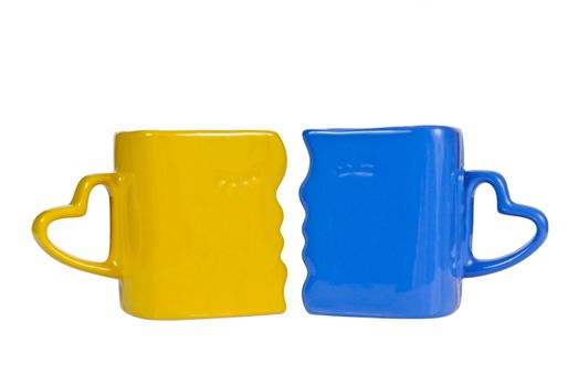 Yellow and blue mug with the handle in the form of heart, isolated on a white background