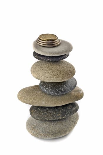 Stability, wealth and welfare - stone stack with coins