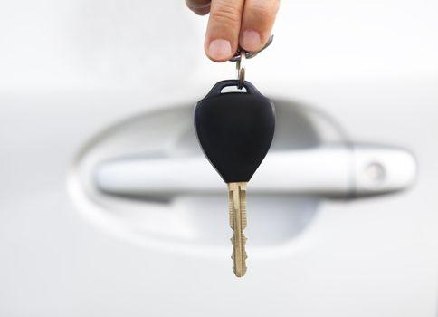 hand holding car key before door of car