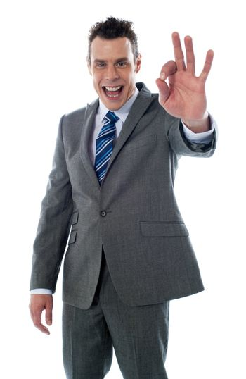 Handsome corporate man gesturing excellent againgt white background