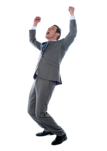 Successful businessman celebrating with arms up isolated over a white background