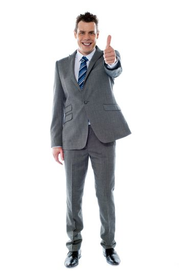 Confident businessman gesturing thumbs up isolated over white