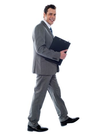 Handsome young businessman with notepad and pen, walking pose