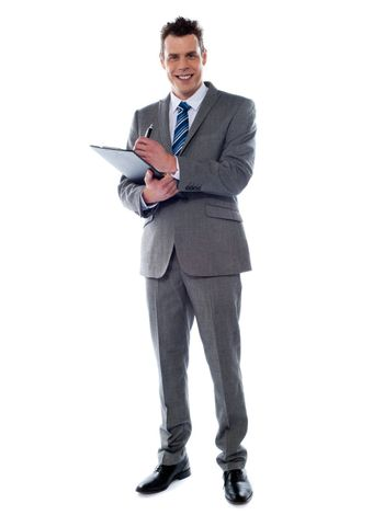 Smiling businessman writing on clipboard isolated over white