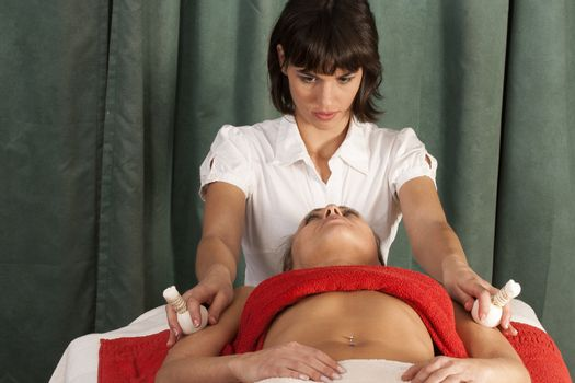 Young woman relaxing in the treatment of your body with herbal
