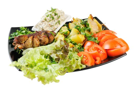 Grilled meat and potatoes. Decorated with tomatoes, lettuce and herbs. Isolated on white