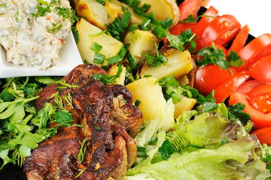 Grilled meat and potatoes. Decorated with tomatoes, lettuce and herbs.