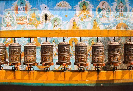 Buddhist prayer wheels with ancient art wall, Nepal