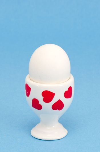 white egg in a special cup for eating covered with red hearts on blue background isolated.