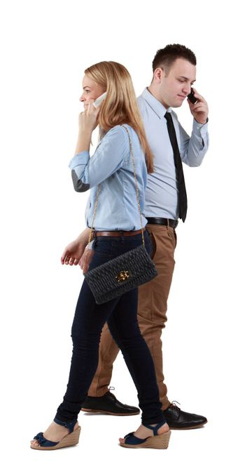 A man and a woman using mobile phones passing by themselves, against a white background.