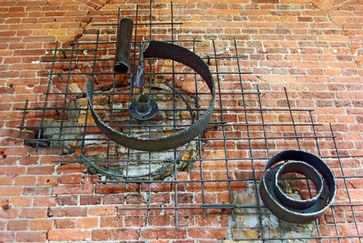 Decorative iron works on weathered brick wall