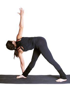 full-length portrait of beautiful woman working out yoga exercise utthita trikonasana on fitness mat