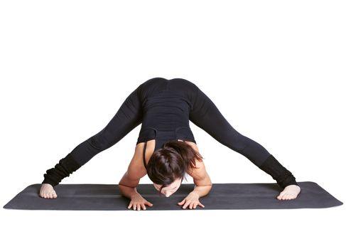 full-length portrait of beautiful woman working out yoga exercises prasarita padottanasana on fitness mat