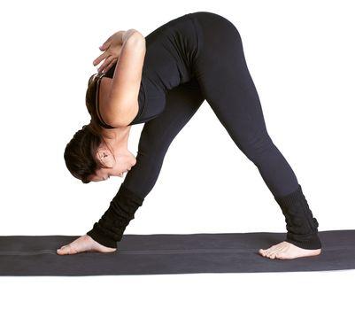 full-length portrait of beautiful woman working out yoga parshvottanasana exercises on fitness mat
