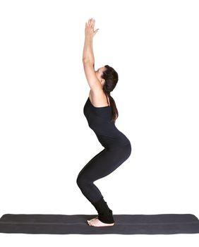 full-length portrait of beautiful woman working out yoga exercise utkatasana on fitness mat