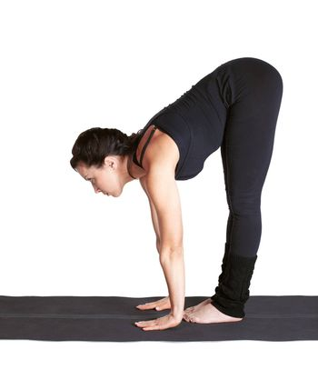 full-length portrait of beautiful woman working out yoga exercises padangushthasana on fitness mat