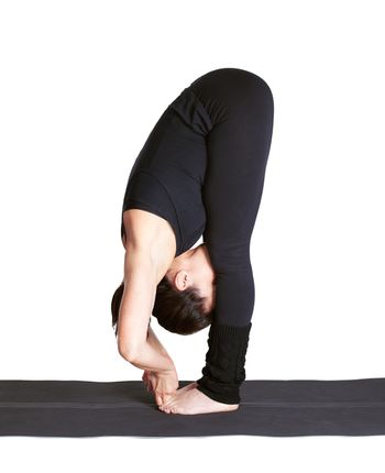 full-length portrait of beautiful woman working out yoga exercise padangushthasana (hands to feet pose) on fitness mat