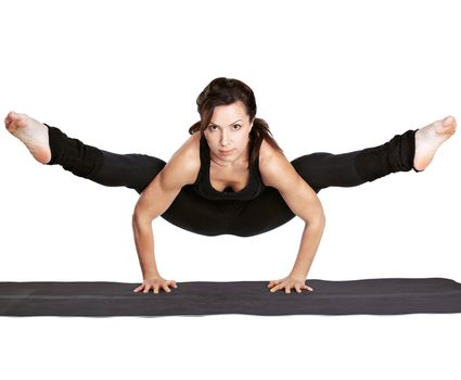 full-length portrait of beautiful woman working out yoga exercise tittibhasana - standing on hands ad doing the spilts on fitness mat