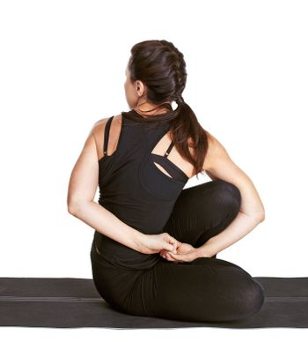 full-length portrait of beautiful woman working out yoga exercise ardha matsyendrasana (half spinal twist) on fitness mat