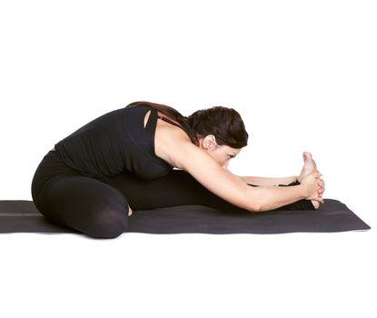full-length portrait of beautiful woman working out yoga exercises Janu shirshasana on fitness mat