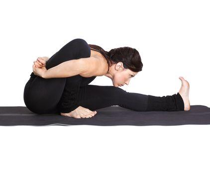full-length portrait of beautiful woman working out yoga exercises Marichiasana pose on fitness mat