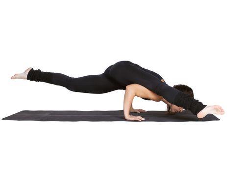 full-length portrait of beautiful woman working out yoga exercises kaundiniasana pose on fitness mat