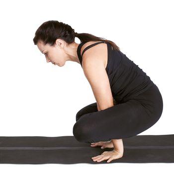 full-length portrait of beautiful woman working out yoga exercise kukkutasana on fitness mat