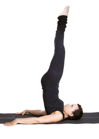 full-length portrait of beautiful woman working out yoga exercise sarvangasana (shoulder stand) on fitness mat